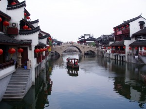 example of peaceful and harmonious Chinese culture photo of a gondola like boat in water between historic buildings on a cloudy day
